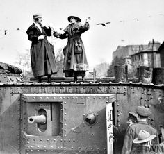 """WWI, 4-9 March 1918; Singers Beattie and Babs, after investing £1300 on the top of the Mark VI tank 130 """"Nelson"""", singing a song which was greatly appreciated by the crowd during the Tank Bank in Trafalgar Square. Cropped. © IWM (Q 54381)"""