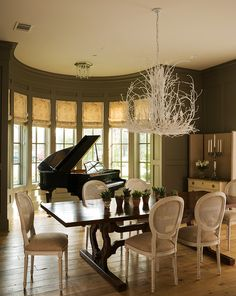 Louis-style dining chairs contrast with weathered oak floors, a casual trestle table, and an edgy painted twig chandelier.