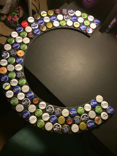 "I collected a bunch of beer bottle caps and after I got a wooden ""C"" made (for my boyfriend Cody) I spray painted the letter black and then glued the caps on! Great 21st birthday gift for a guy! And cheap!"