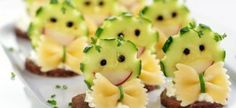 Happy Faces - Rye bread round, herb cream cheese spread, cucumber face with radish lips and peppercorn eyes, pasta bow tie with green chive center