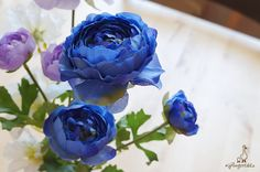 """Blue Ranunculus Each stem measures approx. 15"""" in length. In total there are THREE flowers: Large – approx. 3.5"""" wide Middle – approx. 2"""" wide Small – approx. 1.5"""" wide  The listing is for ONE stem. Available in four colors: 1. Peach (sold out) 2. Lavender 3. Blue 4. Dark Red  ** This ranunculus can be ordered WITH or WITHOUT the stems. {Perfect for} - bridal headpiece, bouquet, wedding crown, corsage and boutonniere - hair piece and millinery hat making - gift packaging - wedding…"""