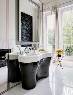 In the master bath, a work by Aaron Curry is reflected in the mirror; the vanity is by Bonetti, and the sink fittings are by Grohe | archdigest.com