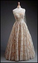 1953 Queen's Tour of the Commonwealth. Norman Hartnell  one-shoulder gown in the crinoline style. The dress was made of gold lamé overlaid with lace and embroidered with gold thread.