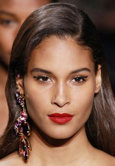 At Elie Saab Tom Pecheux gave the models an above-lid cat eye with berry-colored lips. Orlando Pita swept the hair into a deep side part for romantic, Veronica Lake waves.