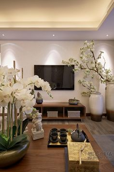 Really loving the idea of putting a potted plant of orchids, a table lamp and a tea set sitting on the wooden side table with the candelabra hanging on the wall above in the living room