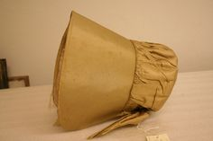 """Large bonnet with cardboard base covered in yellow silk; smooth over brim, ruffled in back; white silk lining inside brim."" 9.5"" x 8.75"" wide x 9.5"" long. ca. 1810. Litchfield Historical Society, Connecticut"