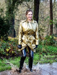 Gold metallic raincoat latex pants and rubber boots in water