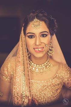 Bridal Portraits - Bride in a Peach Wedding Lehenga with Gold Jewelry | WedMeGood | Peach Blouse with Mukaish Work, Gold Maang Tikka, Necklace and Nath #wedmegood #indianbride #indianwedding #indianjewelry #jewelry #lehenga #bridal #portrait
