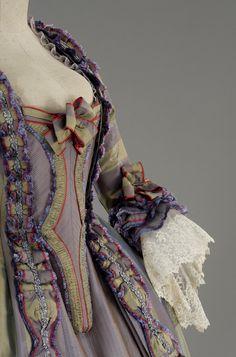 """""""Robe à la française"""" composto da corpino in taffettas cangiante lilla, guarnito con bouillonné e fiocco in shantung color salvia. Gonna dello stesso tessuto, decorata con fascia bouillonnè e con pedana di"""