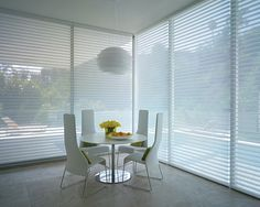 Without color, form, shine and sleek design makes a greater impression with this all white dining room.  Silhouette® window shadings ♦ Hunter Douglas window treatments