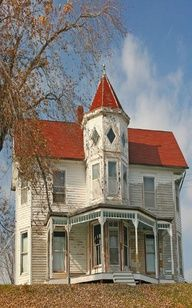 The roof draws attention, looks restored yet just as abandoned as the rest of the dwelling. Odd architectural design with the turret centered over the porch.