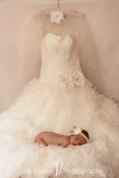Newborn on wedding dress. Done by one of my favorite Photogs of all time!