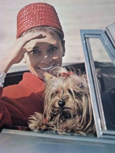 Audrey Hepburn in a convertible with her Yorkshire Terrier, Mr. Famous.