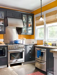 Knocking out part of the wall between the kitchen and dining space ushered in practical function. Homeowners stayed true to the room's 1906 architecture with the cabinetry and window proportions. A punchy orange and navy color palette adds modern appeal./