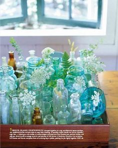 Vintage bottles add patinas of blue and brown for subtle color on our reception tables