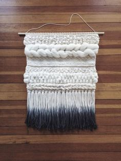 This is a hand woven wall hanging in a palette of creamy neutrals. The ends of the fringe are dip-dyed grey.  The dowel is 24 inches wide, and the