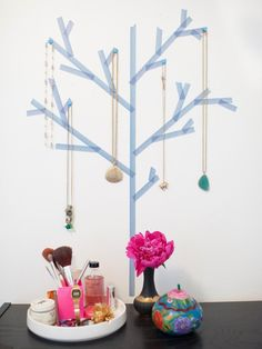 Blue pins hold jewelry on the blue washi tape tree design on this girl's room wall. The tape serves as a fun way to display and store jewelry easily above the dark wooden dresser.