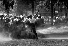 """Bob Adelman, Kelly Ingram Park, Birmingham, 1963.  """"The police and firemen used a brute show of force to try to stop the ongoing demonstrations. It didn't work on this day. Rather than fleeing, the protestors hung on to each other and were able to stand up to the full fury of the water, though not without casualties. I have never witnessed such cruelty. There was almost as much moisture behind the lens as in front."""""""