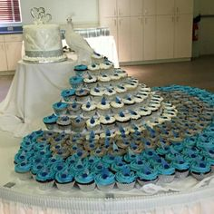 Peacock cupcake tower - how beautiful! The cupcakes are simple, with coordinated shades and fondant feathers. could be made large (like this wedding cake) or small.