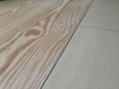 Enkelt overgang i niveau fra trægulv til klinker - adskilt med lodret stålskinne. Gulvene er i 30cm douglas gran-planker fra Dinesen og 60x60cm klinker fra Casalgrande Padana.