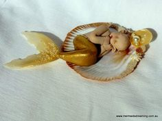 Orelia (meaning golden) is a handmade one-of-a-kind polymer clay mermaid baby.  Made by Vanessa Witschi of Mermaids Dreaming at www.facebook/com/mermaidsdreaming