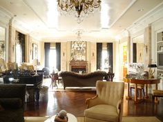 The living room's floor to ceiling windows are covered in drapes made out gold and brown satin fabric from Lee Jofa. Nearby one of a pair of wood framed chairs that came from an old  French cruise ship.   French Empire chandeliers and sconces illuminate the grand living room space.