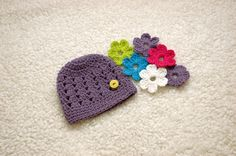 What a great idea!!  interchangeable by putting the flowers on the button.    I've mad a jillion hats with the little flowers but never thought to put a button to change them out!