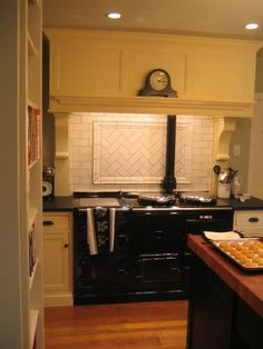 Vintage look kitchen with cream cabinets, subway tile backsplash, soapstone counters, a black #AGA range and a black island with a butcher block counter -- Bluebell Kitchens, bluebellkitchens.com
