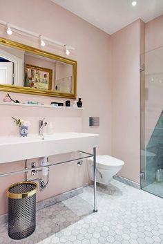В ванной мрамор на полу холодного серого оттенка приглушает яркость пыльно-розового цвета стен. Это очень красивое сочетание, и общий эффект комнаты — атмосфера спокойствия, тепла и расслабленности. Душ за стеклянной дверью привлекает внимание своей необычной треугольной формой, а золотые детали декора ещё раз утверждают роскошь как обязательный элемент дизайна этой квартиры.