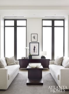 """""""Balance and repetition was key to this space,"""" explains Brown, who outfitted the sitting area with dark woods and neutral fabrics. The designer devised the pair of custom cocktail tables, which are bracketed by matching Verellen sofas."""