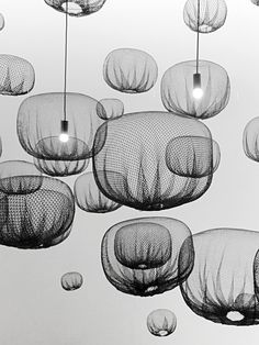 pendant lights that softly emit light, in the manner of traditional Japanese paper lanterns | 'farming-net lamp', by nendo