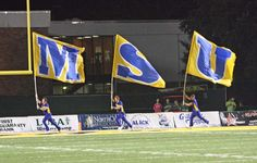 The cheerleaders running with the flags