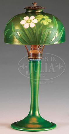 James D. Julia, Inc. -  RARE Tiffany Studios Intaglio Cut Lamp. Lamo begins with a green favrile glass shade that is intaglio cut in several layers in colors of soft green, medium green and vibrant white depicting a floral design with long stem foliage. SHade is finished with a white cased liner for proper illumination. Supporting the shade os a single socket green favrile glass base. Shade and base each have a n outstanding, matching iridescent finish that shows the spectrum of the colors.