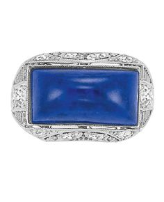 An Edwardian Platinum, Lapis and Diamond Ring. One oblong cabochon lapis ap. 15.1 x 7.3 x 5.2 mm., c. 1910.