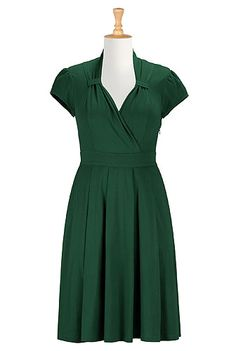 Our soft knit dress inspired by vintage styling is fashioned with a banded waist and a cross-over sweetheart neckline looped at the sides. <li>Slips on over head, partial side zip closure. <li>High neck back. <li>Cap sleeves with ruched shoulders. <li>Elastic smocked back waist. <li>Box-pleated skirt. <li>Side seam pockets.  <li>Below knee length. <li>Cotton/spandex, jersey knit, light stretch, midweight. <li>Machine wash.