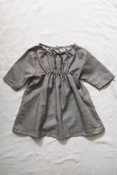 Makie contemporary grey dress with detail waist and short sleeves. Thin bow. Button in back. Simplicity.. (Winnie)
