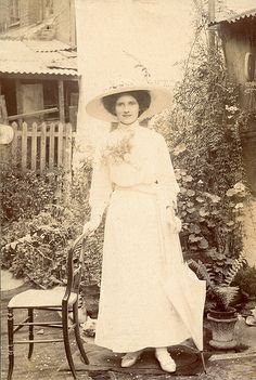 Edwardian lady with a parasol and a chair in the garden