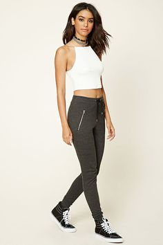 A pair of knit sweatpants featuring a drawstring waist, ribbed trim, and two front zippered pockets.