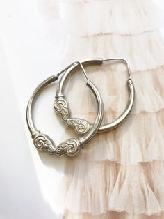 These are sure to be go-to pieces in your wardrobe, given their size and subtle detail. Two rams heads meet face-to-face at the bottom of each hoop. This ram motif is very Tibetan feeling, or even Western like a bighorn sheep. Since these hoops are hollow, they are surprisingly lightweight for their size. HISTORY: Light modern vintage, lightly used.  MATERIALS: Sterling silver  SIZE: These hang a full 2 from the ear, and measure slightly over 1.5 in width of the hoop. They weigh 7.3 g each…