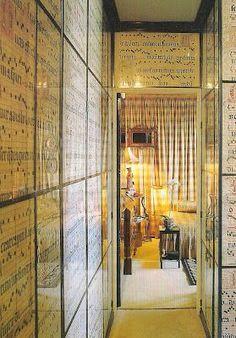Pasillo en casa de Pierre Delbée en Paris. Paredes forradas con páginas de libros de canto gregoriano enmarcados tras un cristal.