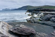 Waterfall falling straight to the sea on the Valentia Island in Ireland with some amazing rocks in the foreground