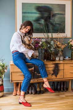 """Thursday: """"I love pairing bright details with simple looks or casual materials like denim or cotton. Here the reddish colors of my shoes and belt stand out against my blouse and jeans. Perfection!"""" Merlette blouse, $380, Merlette; Rouje jeans, $150, Rouje"""