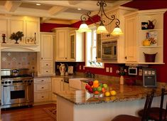 Kitchen: Red walls, cream cabinets with darker fixtures, dark countertops, wood floor stainless appliances.
