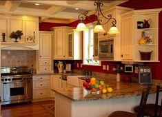 Kitchen: Red walls, cream cabinets with darker fixtures, dark countertops, wood floor stainless appliances.