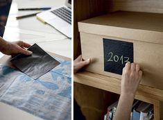 """""""Na estante, caixas de papelão com etiquetas arquivam os projetos da arquiteta, uma ideia simples para pôr ordem em papéis: recorte quadrados de adesivo vinílico preto fosco (Con-Tact, da Vulcan) no tamanho adequado a suas caixas. Cole as etiquetas e escreva com giz escolar. Se precisar renomear, apague com pano úmido."""""""