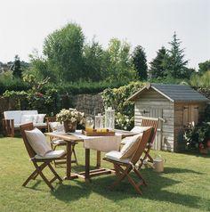 En un pequeño jardín  Una mesa y 4 sillas plegables de madera para un comedor muy práctico. Junto al comedor, una casita de madera para guar...