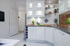 biała kuchnia skandynawska ze ścianą z czerwonej cegły i biała podłogą z desek,
