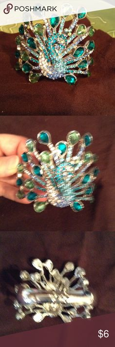 Bracelet Rhinestone peacock bling bangle! It's missing a tiny stone on bottom right feather. You really can't tell but I want to disclose this information. So cute though! Clasp springs closed in last picture. The stones are clear, aquamarine colored, turquoise colored & peridot colors. Jewelry Bracelets