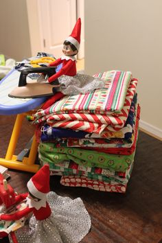 Sitting on a big pile of Christmas Themed fabric while ironing out one of the projects they are working on together.