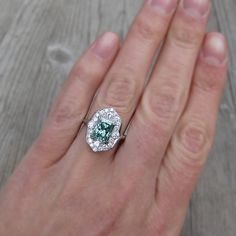 2.3ct Radiant Green Moissanite Engagement Ring with diamond halo in 14k recycled white gold.